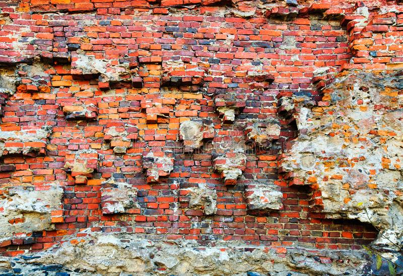 Damaged brick wall of red color. Vintage background, old weathered texture. Shabby surface of grunge masonry. Vintage facade. stock photos