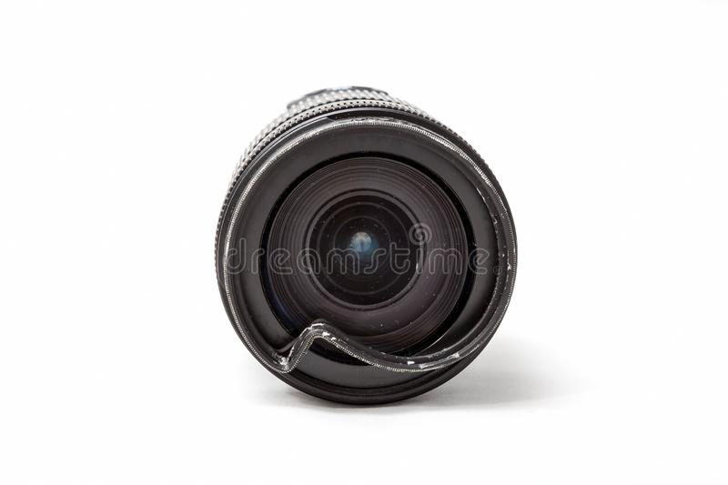 Damaged and broken zoom lens for the digital camera, dented protective UV filter. Front close up view To be repaired. Isolated on stock images