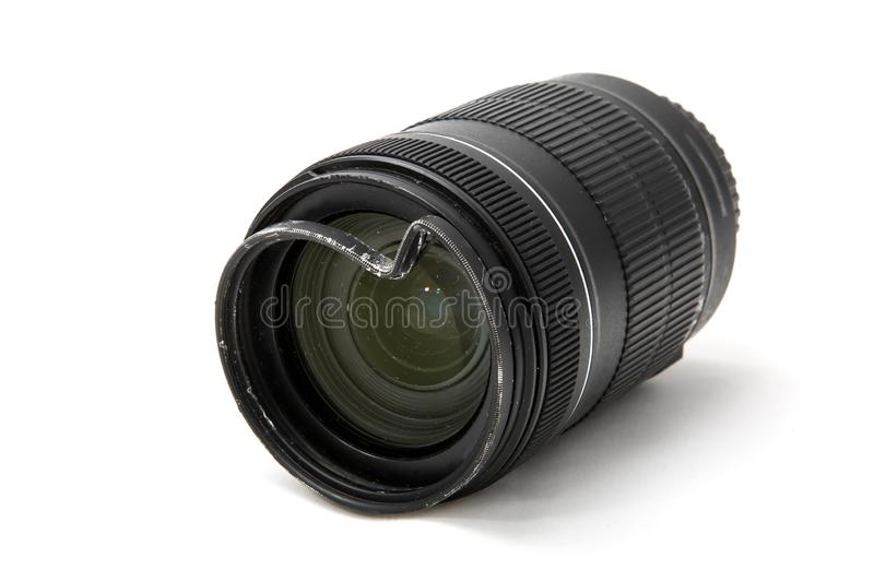 Damaged and broken zoom lens for the digital camera, dented protective UV filter. Front side view. To be repaired. Isolated on stock photography
