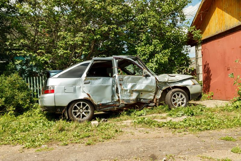 Damaged car after accident near garage in the yard. Crash, automobile, broken, bumper, danger, metal, repair, road, traffic, vehicle, wreck, body, dangerous stock photo