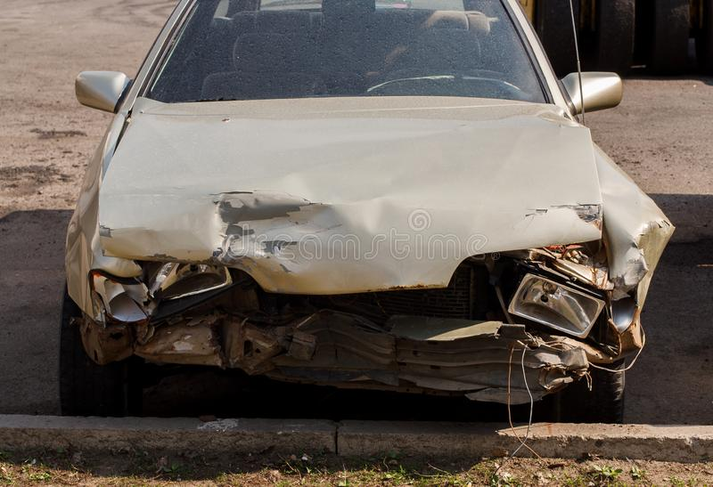 Damaged car with front end smashed after a crash accident parked on the street. Damaged silver car with front end smashed after a crash accident parked on the royalty free stock photos