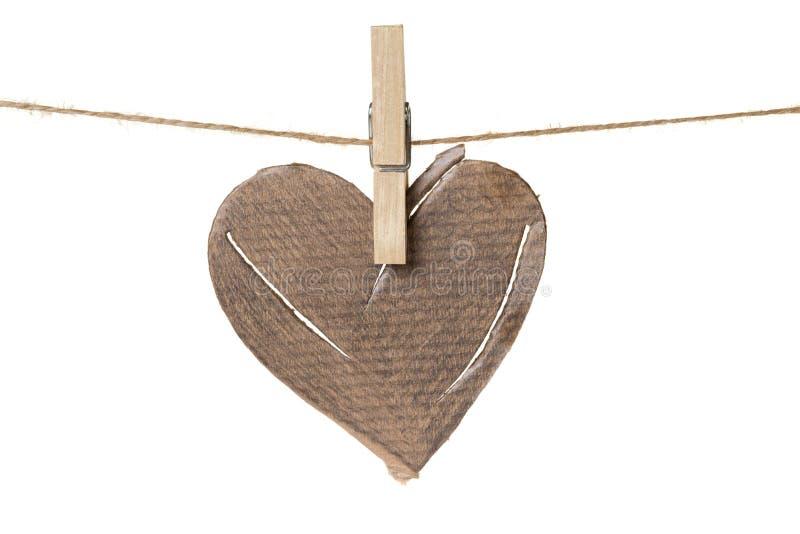 Damaged cardboard heart hanging. Isolated on white stock images