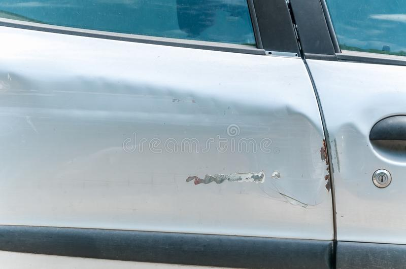 Damaged doors of silver car with scratched and peeled paint in crash accident and collision close up royalty free stock photos