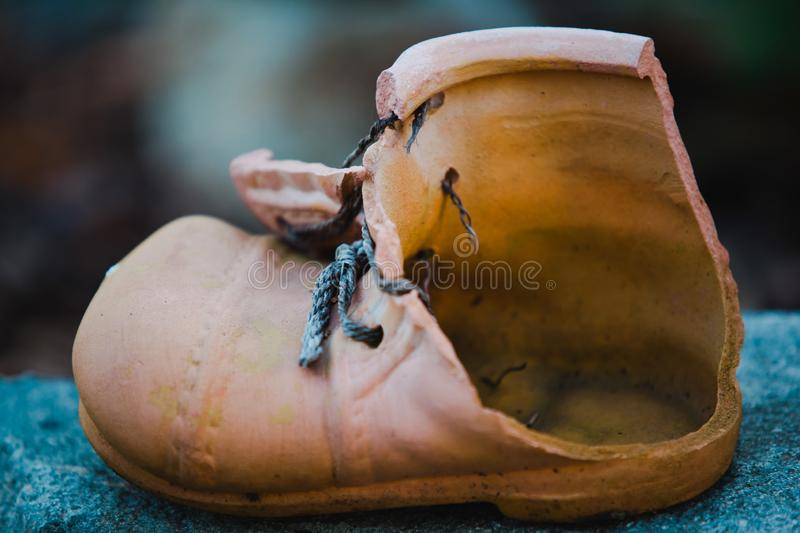 Damaged flowerpot piece - boot like shape stock images