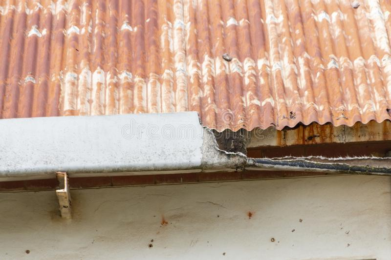 A damaged gutter on a rusted tin roof stock image