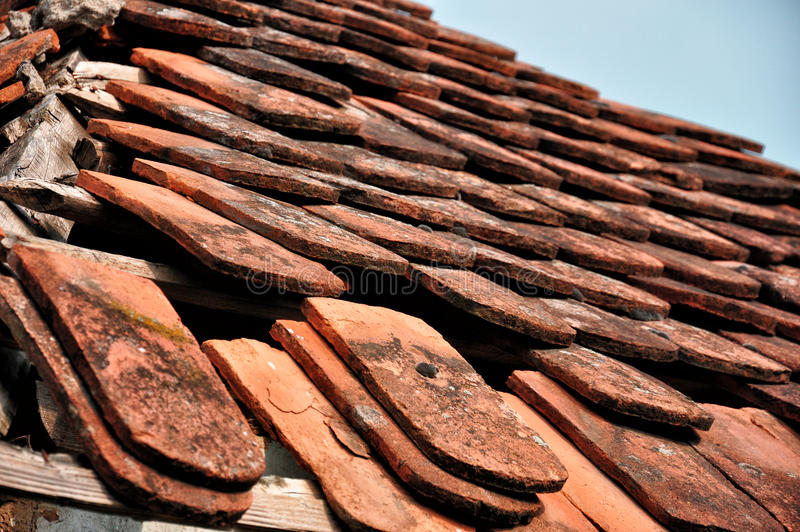 Damaged house roof. Old damaged roof on a house with blue sky stock image