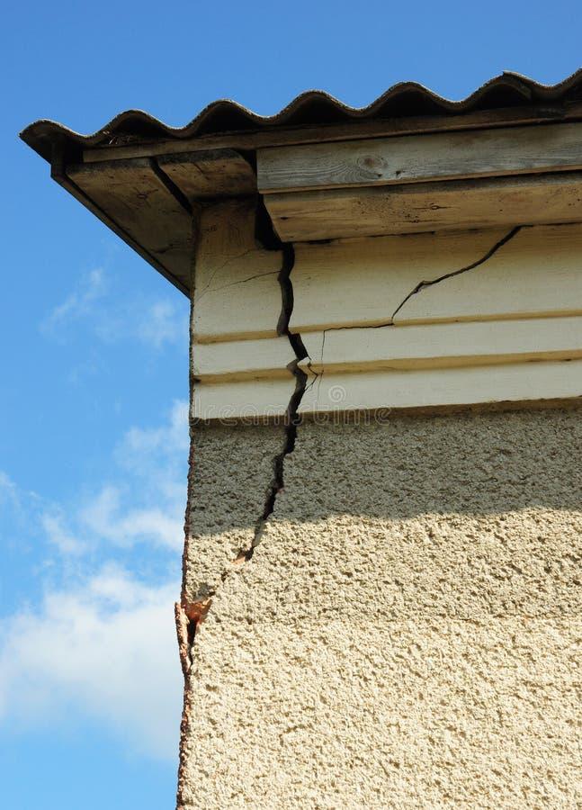 Damaged house stucco wall corner. Cracked Wall near Roof Construction. stock photos