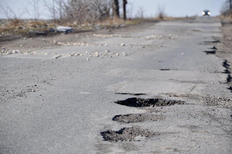 Damaged road. Full of cracks and holes royalty free stock photo