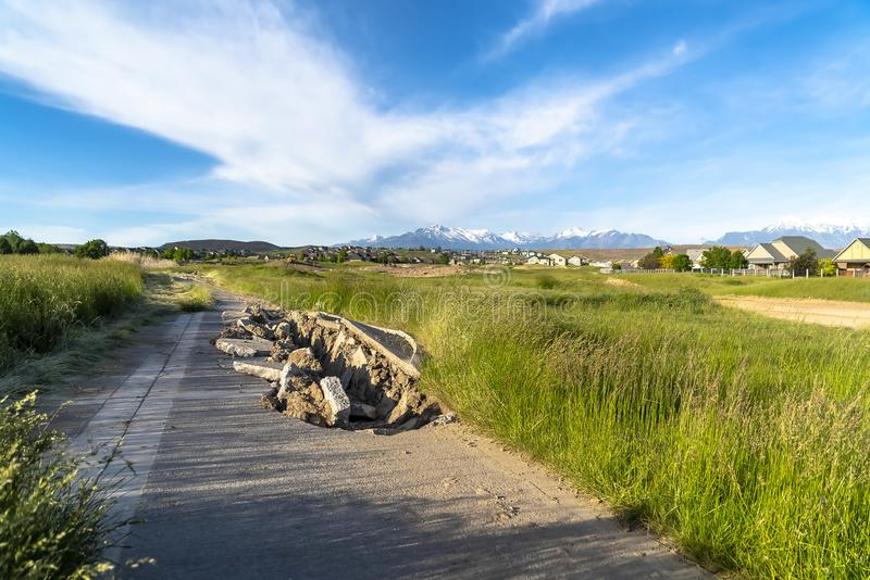 Damaged road with a huge hole amid grassy terrain and houses on a sunny day. A snow peaked mountain under blue sky can be seen in the distance royalty free stock image