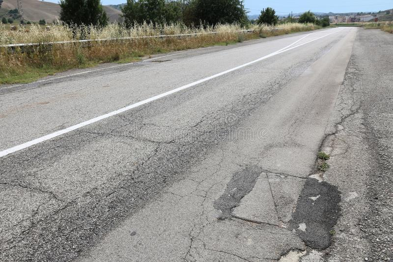 Damaged road. Road surface damage - bad maintenance quality. Asphalt cracks in Italy stock images