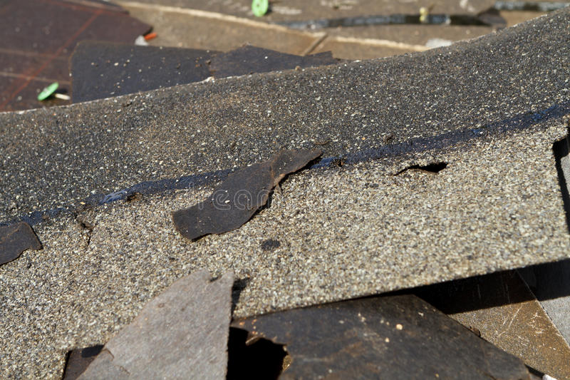 Damaged Roof Shingles Trash Pile. Shallow depth-of-field, close-up shot of a trash pile of old asphalt roof shingles and tar paper removed during a residential royalty free stock images