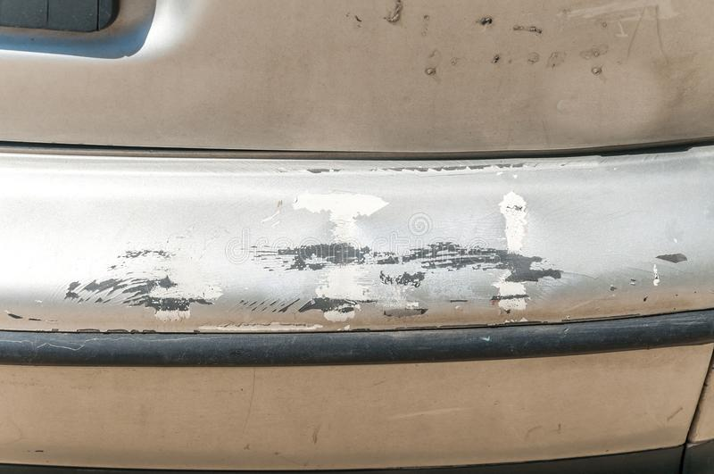 Damaged silver car front bumper with scratched and peeled paint close up stock photography