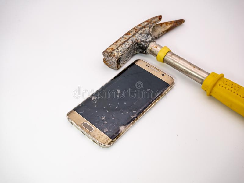 Damaged smartphone disply with hammer and white background royalty free stock image