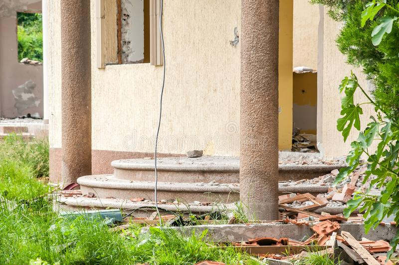 Damaged stairs and wall of domestic civilian villa house or building with hole without windows and doors destroyed by grenade in t stock image