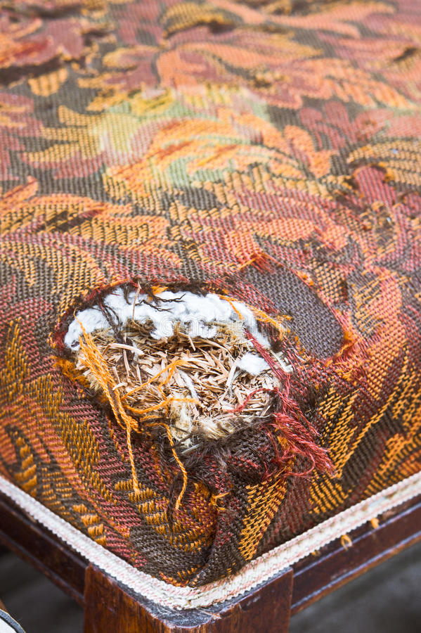 Damaged upholstery. Torn cover of the corner of an antique chair stock photos