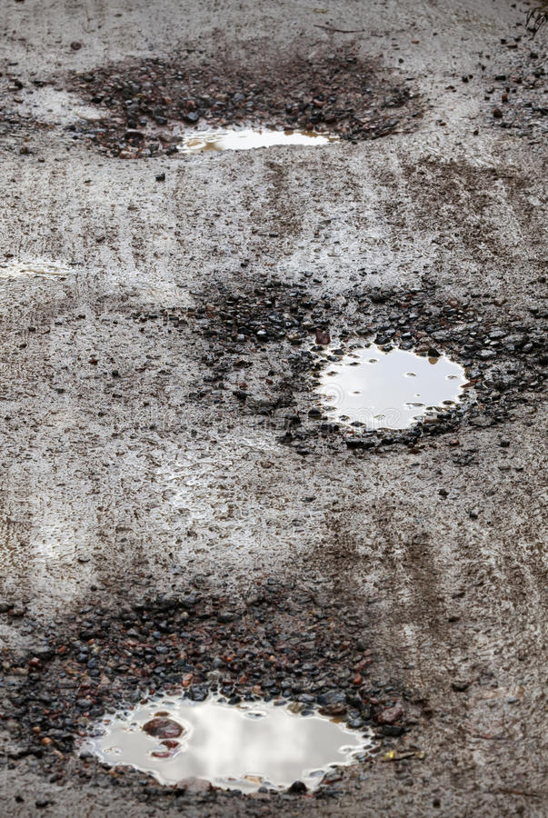 Damaged wet road with holes. Texture of damaged wet road with holes royalty free stock images