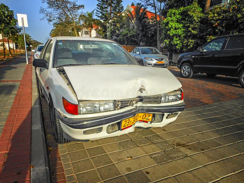 Damaged white car stands on the pavement after the collision stock photography