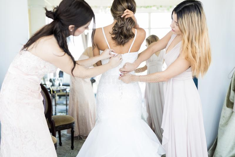 Damas de honor que ayudan a la novia en conseguir listo fotos de archivo