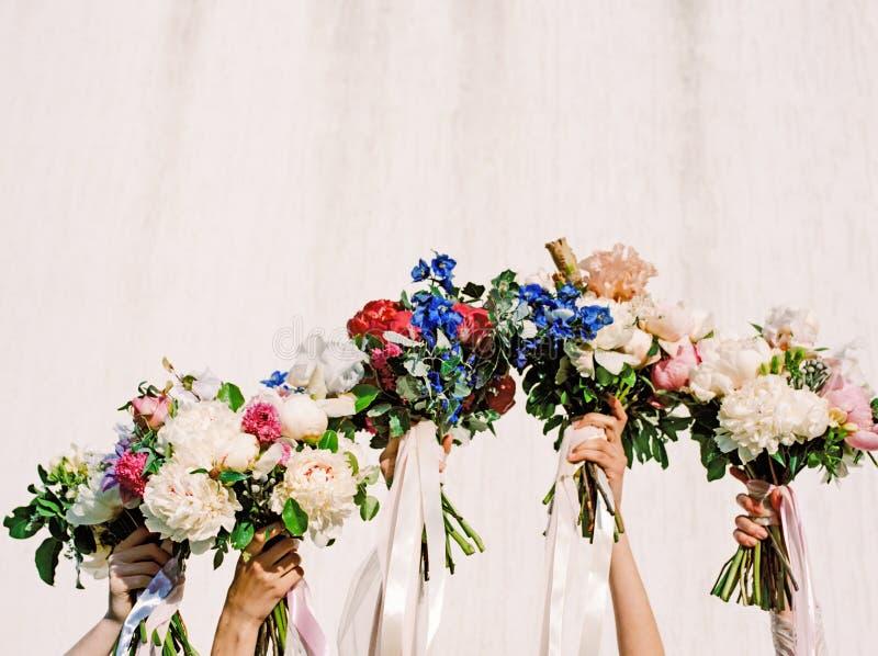 Damas de honor que llevan a cabo concepto que se casa feliz al aire libre de los ramos de la boda fotografía de archivo