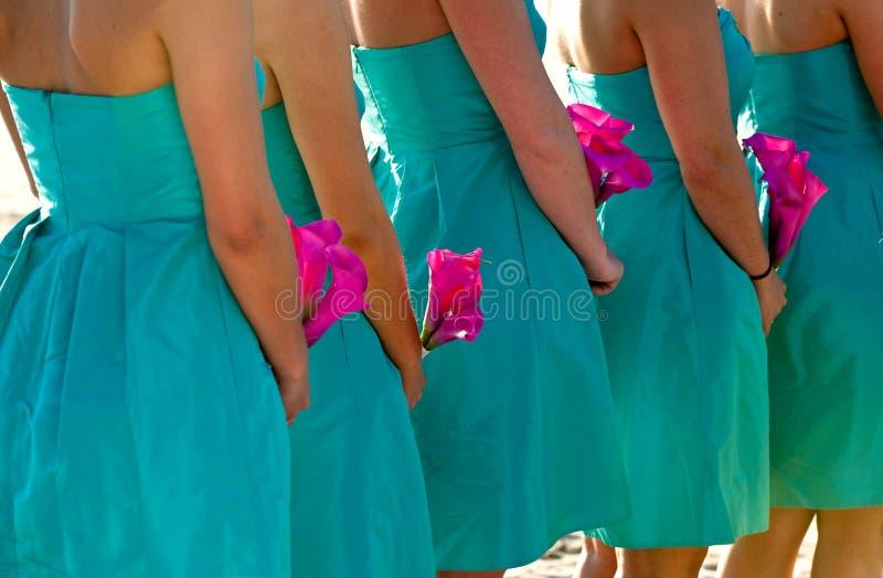 Damas de honor que sostienen las flores del color de rosa caliente imagenes de archivo
