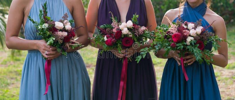 Damas de honor que sostienen las flores en sus manos fotos de archivo