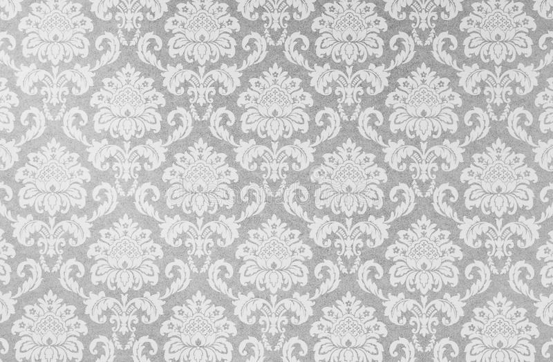 Damask repeat pattern on old paper. A closeup of an old fashioned shabby grey and white damask flower pattern printed on a paper background stock photos