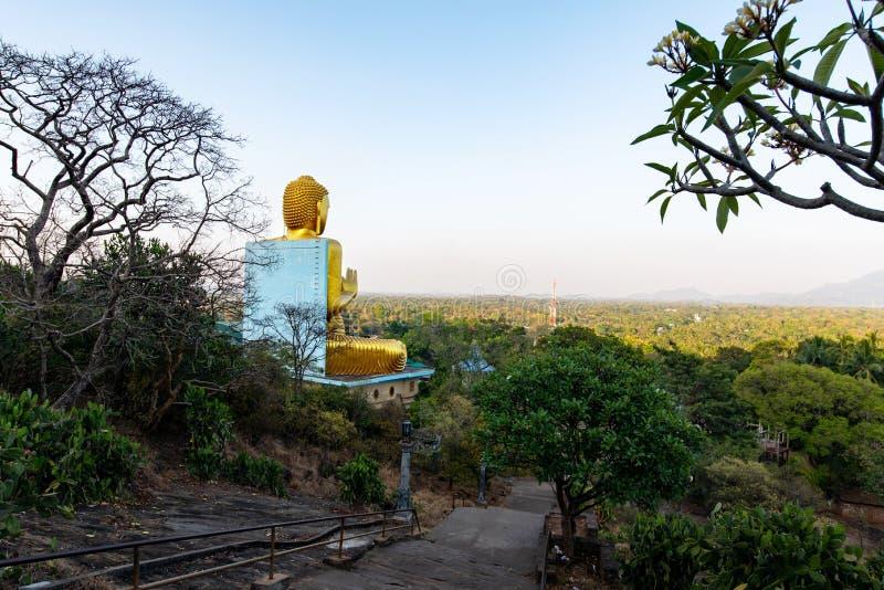 Dambulla,斯里兰卡- 2019年3月30日:有大菩萨雕象的金黄寺庙在斯里兰卡 图库摄影