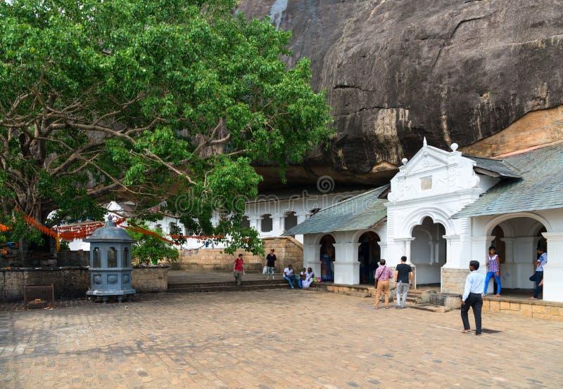 Dambulla golden temple cave complex buildinds is destination for. DAMBULLA, SRI LANKA - NOV 2016: Holy tree and Golden temple cave complex buildinds carved in stock images