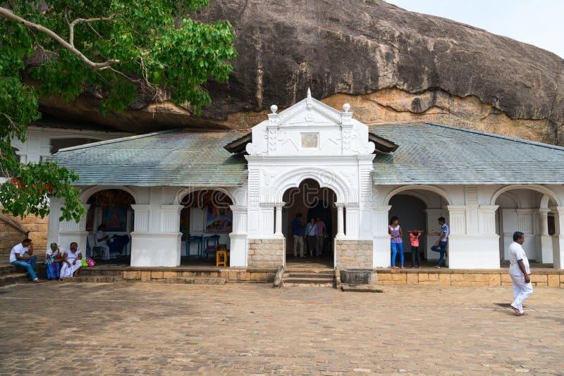 Dambulla golden temple cave complex buildinds is destination for. DAMBULLA, SRI LANKA - NOV 2016: Golden temple cave complex buildinds carved in the rock is royalty free stock photography