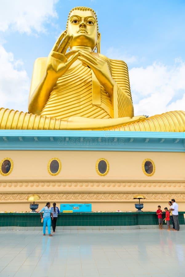 Big golden Buddha statue in wheel-turning pose in Dambulla Golden temple. DAMBULLA, SRI LANKA - NOV 2016: Local people near Big golden Buddha statue in wheel royalty free stock image