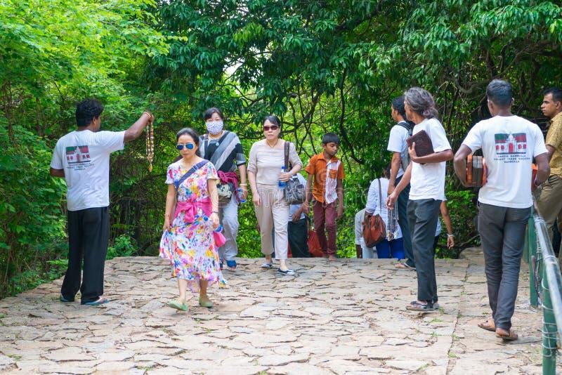 Obtrusive souvenir dealers propose their goods to tourists. DAMBULLA, SRI LANKA - NOV 2016: Obtrusive souvenir dealers propose their goods to tourists on a way royalty free stock photo