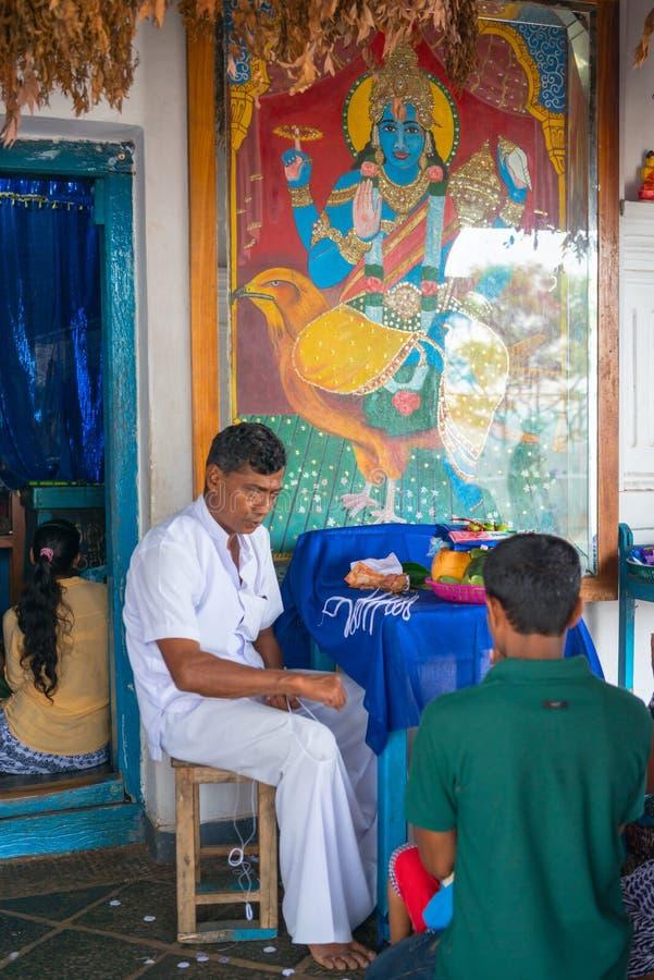 Priest in small Vishnu shrine in Dambulla Golden cave temple. DAMBULLA, SRI LANKA - NOV 2016: Priest in small Vishnu shrine in Golden cave temple prays with stock photos