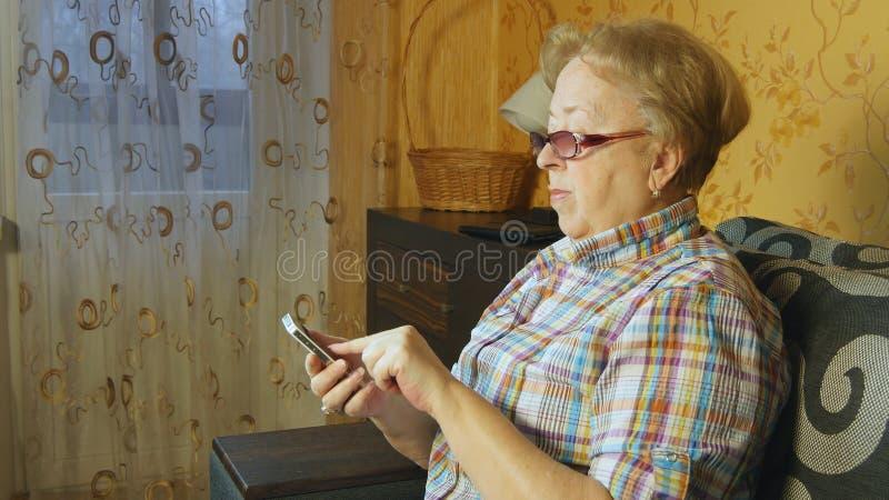 Dame âgée à l'aide du smartphone à la maison images libres de droits