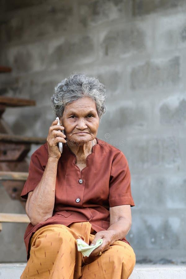 Dame âgée asiatique parlant au téléphone portable photographie stock libre de droits