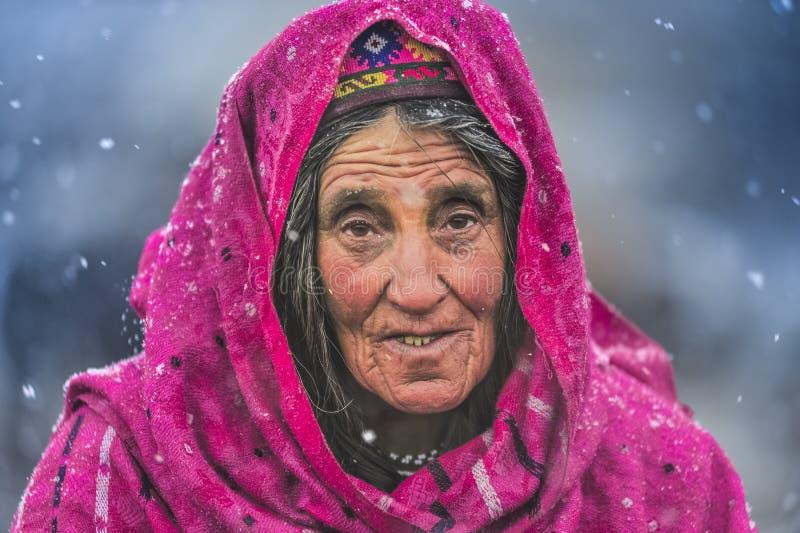 Dame âgée au milieu des animaux de attente de neige à retourner du pâturage image stock