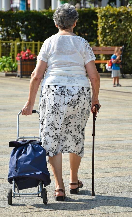 Dame âgée avec le panier sur la rue images libres de droits