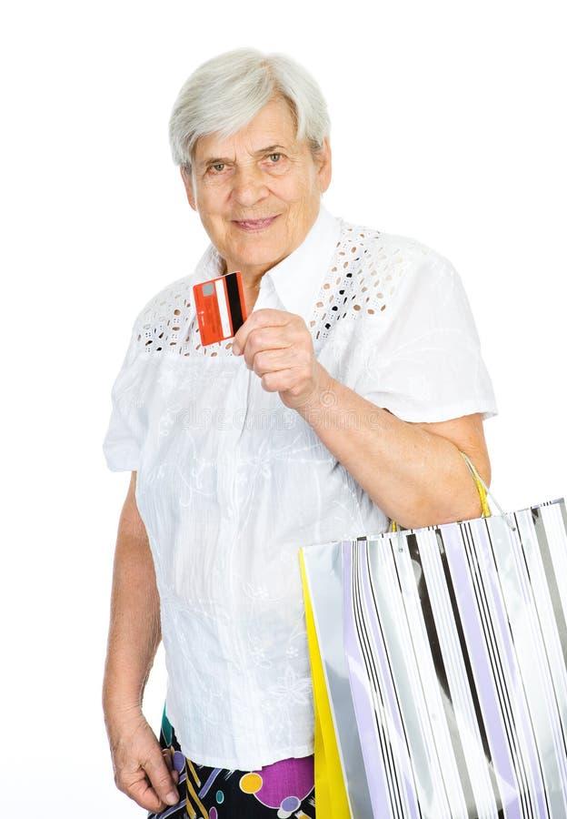 Dame âgée avec les paniers et la carte de crédit. photos stock