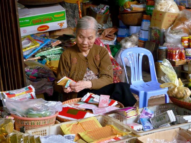 Dame âgée comptant l'argent dans sa stalle sur un marché local photographie stock
