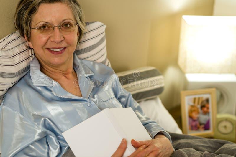 Dame âgée dans des pyjamas se situant dans le lit image stock