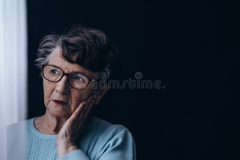 Dame âgée dans la chambre noire photo stock