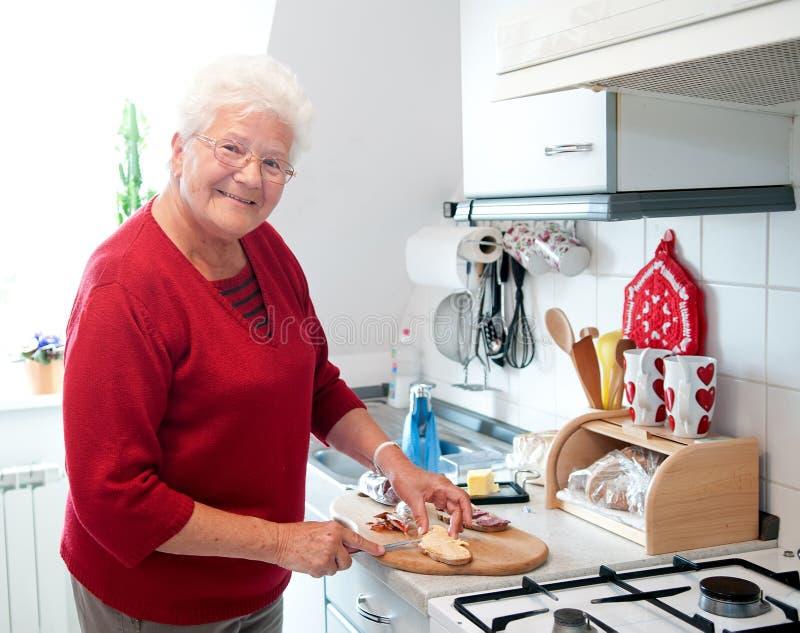 Dame âgée dans la cuisine images libres de droits