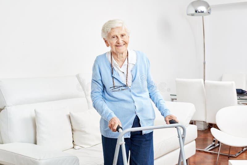 Dame âgée de sourire avec le marcheur apprend à aller photo libre de droits
