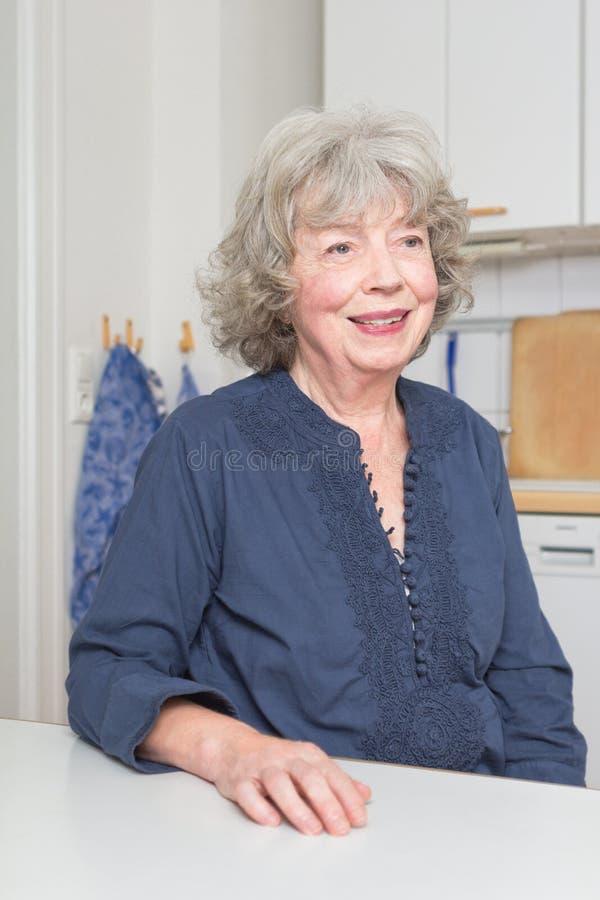 Dame âgée de sourire dans la cuisine photo libre de droits