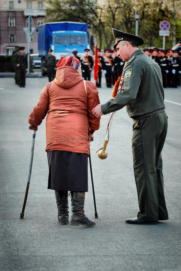 Dame âgée est handicapée le long du système des militaires russes images stock