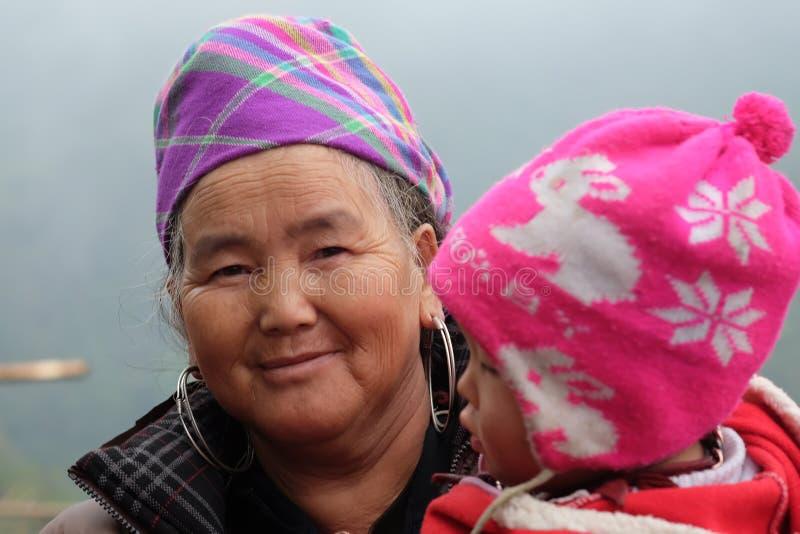 Dame âgée ethnique vietnamienne de H'Mong avec le bébé dans des costumes traditionnels photos stock