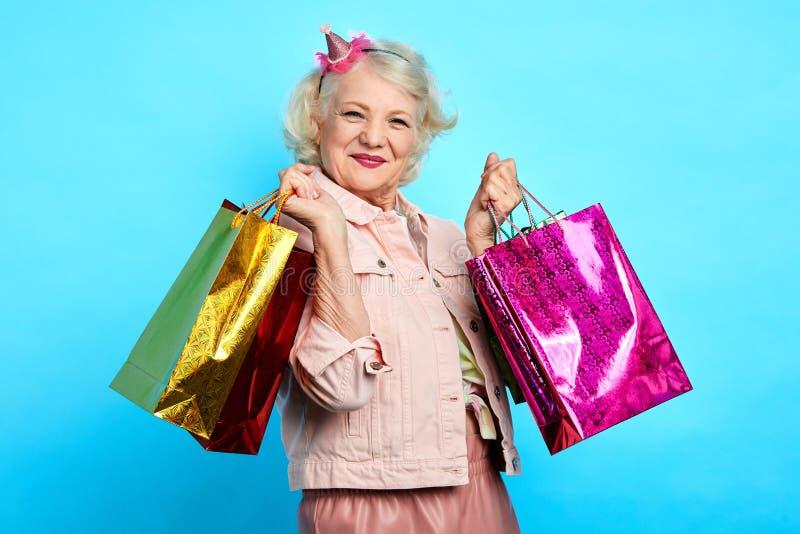 Dame âgée exprime l'émotion positive, fait les achats en fin de semaine image stock