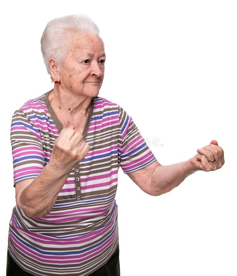 Dame âgée fâchée faisant des poings image stock