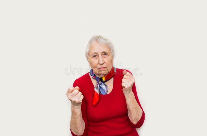 Dame âgée fâchée faisant des poings sur le fond blanc image stock