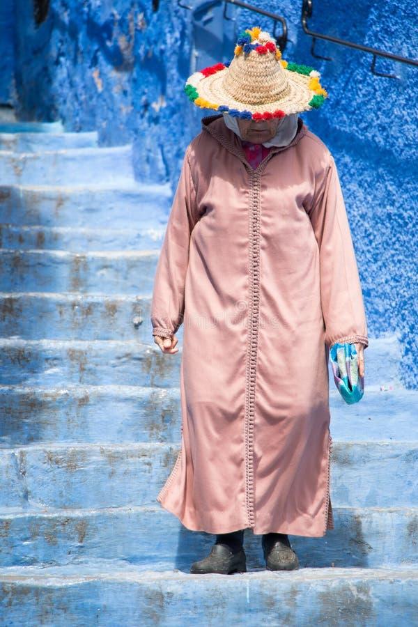 Dame âgée flâne par les rues de Chefchaouen, la ville bleue au Maroc, avec son costume traditionnel photographie stock