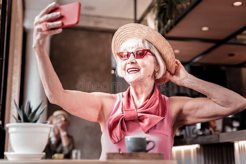 Dame âgée gaie avec le maquillage lumineux et les lunettes de soleil rouges se photographiant photos libres de droits